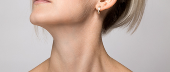 Woman's chin and neck on gray background