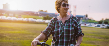 Portrait of mature woman in her sitxies, slightly overweight, enjoying her life and leisure time. Woman is expressing positivity and determination towards life goals. She is riding bicycle in urban part of the city in summer afternoon