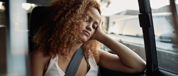 Young woman sleeping on backseat of car